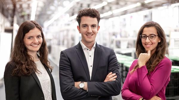 Drei Schaeffler Mitarbeitende und junge Talente im Portrait in einer Werkshalle.