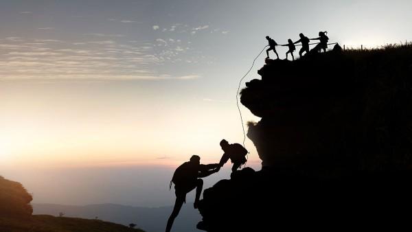 Menschen erklimmen durch Zusammenarbeit und Zusammenhalt gemeinsam einen Berg, der ein neues Ziel symbolisieren soll.